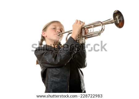 a pretty little girl with a black jacket plays the trumpet on white background - stock photo