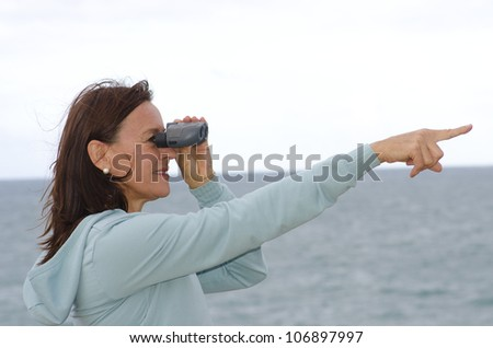 A pretty looking middle aged woman with binoculars standing at seaside and pointing with one arm towards the distance to the right, with ocean and bright sky as blurred background and copy space. - stock photo