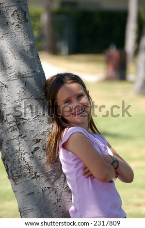 A pretty nine year old girl leaning on a tree in a park. - stock photo