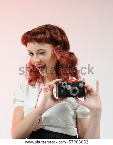A pretty pin-up girl holding a vintage camera on a soft pink background. - stock photo