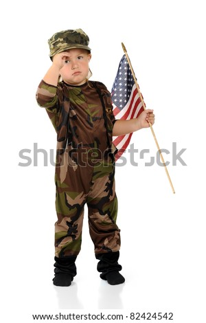 """A pretty preschool """"soldier"""" in army camouflage saluting as she carries an American flag.  Isolated. - stock photo"""