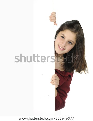A pretty preteen peeking around a white wall and on a white background.   - stock photo