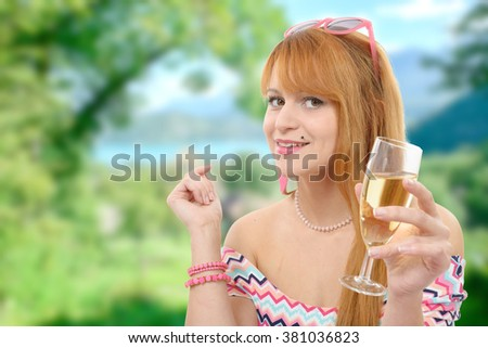 a pretty redhead woman drinks a glass of wine, greenery on background - stock photo