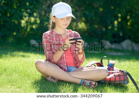 a pretty schoolgirl sitting on the grass playing with his smartphone - stock photo