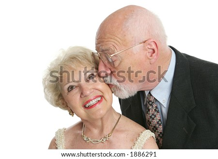 A pretty senior woman giggling as her husband surprises her with a kiss. - stock photo