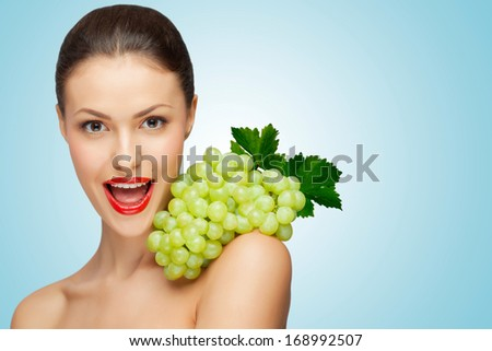 A pretty sexy woman holding a bunch of healthy green grapes on her naked shoulder. - stock photo