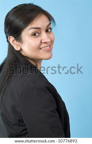 A pretty smiling young woman looking playfully over her shoulder at the camera. - stock photo