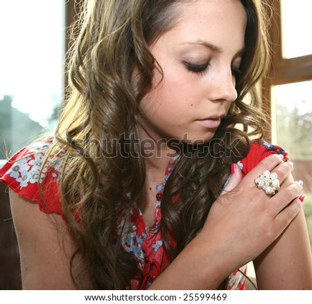 A pretty student looks at her pearl ring - stock photo