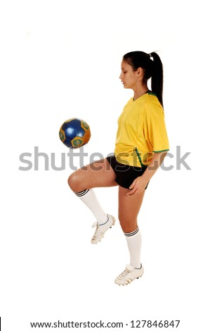 A pretty teenage girl standing in the studio in her soccer uniform and playing with the football, her hair in a ponytail for white background. - stock photo
