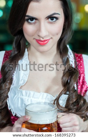 A pretty waitress with beers at the bar - stock photo