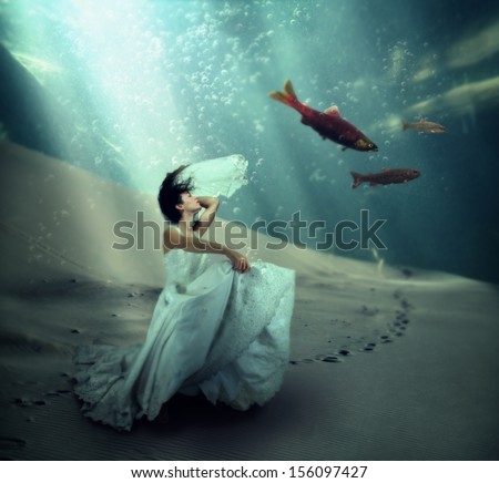 a pretty woman dancing underwater in the ocean - stock photo