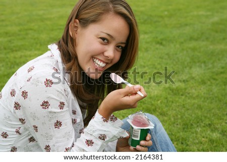 A pretty woman eating yogurt on the grass - stock photo