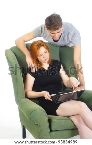 a pretty woman is helping a man with the use of the computer - stock photo