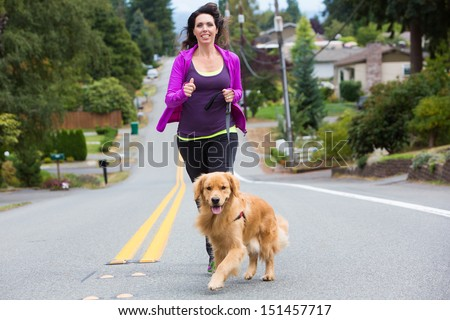 A pretty woman jogging with her golden retriever dog - stock photo