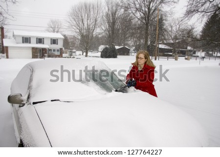 A pretty woman scraping snow off her car during a snowstorm - stock photo