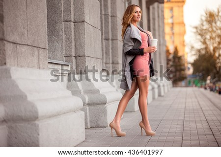 A pretty woman with a coffee to go against urban scene. - stock photo