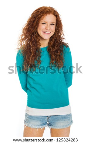 A pretty woman with red hair and freckles wearing short denim shorts. - stock photo