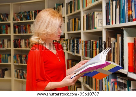 A pretty young adult woman enjoys her book while researching in a library. - stock photo