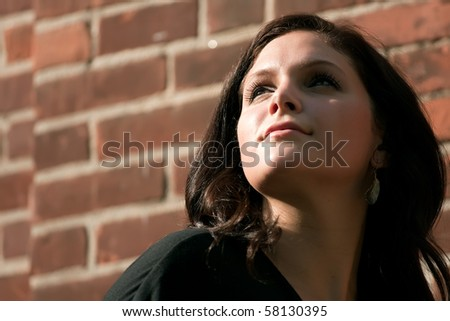 A pretty young brunette woman posing in dramatic lighting outdoors.  Shallow depth of field. - stock photo