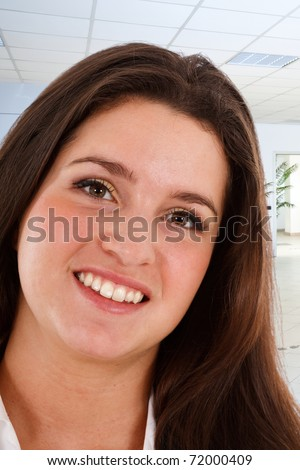 A pretty young businesswoman smiling in her office. - stock photo