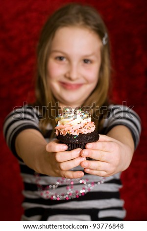 A pretty young child eating a delicious cupcake for dessert. - stock photo