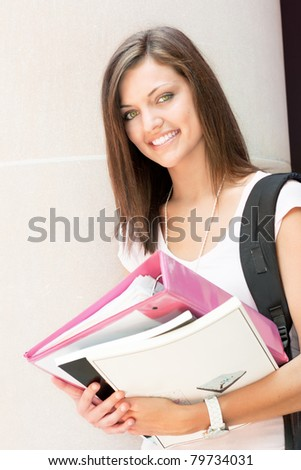 A pretty young college or high school age girl with study materials - stock photo