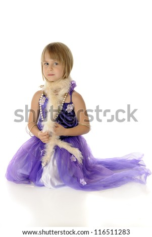 A pretty young girl playing dress-up in a formal purple dress, necklace, bracelets, and a boa.  On a white background,. - stock photo