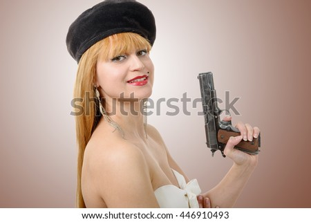 a pretty young sexy woman with a gun  - stock photo