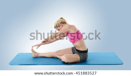 A pretty young slim woman exercising with yoga - stock photo
