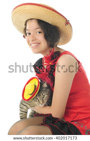 A pretty young teen festively dressed for Cinco de Mayo with her sombrero-wearing kitty.  On a white background. - stock photo
