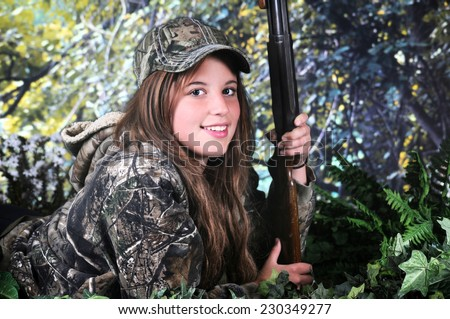 A pretty young teen hunter with a rifle looking at the viewer from her position on the ground surrounded by foliage. - stock photo