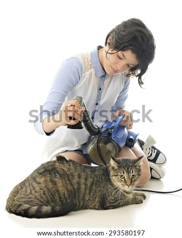 A pretty young teen vacuuming a contented tabby cat with a spot of back hair being suctioned up.  Focus on the girl.   On a white background. - stock photo