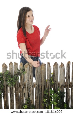 A pretty young teen walking by an old wooden fence while waving hello to her friends.  On a white background. - stock photo