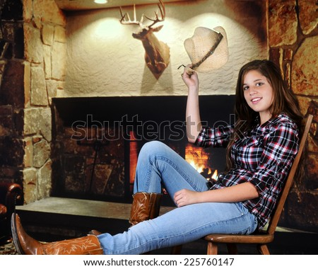 A pretty young teenage cowgirl tipping her hat in greeting as she rests near a fireplace. - stock photo