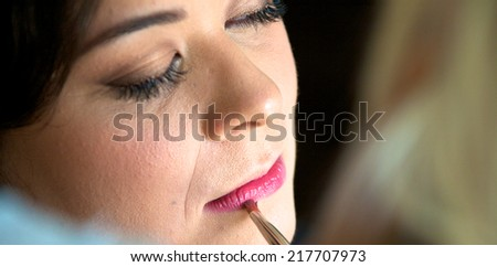 A pretty young woman getting ready for her wedding and having her lipstick applied - stock photo