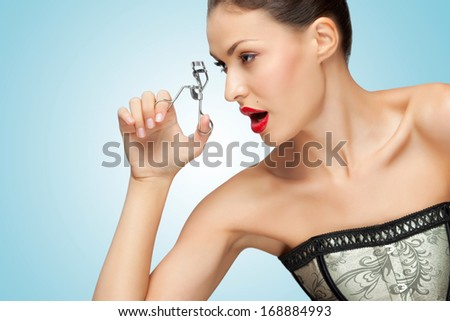 A pretty young woman holding an eyelash curler in her hand. - stock photo