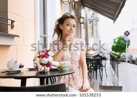 A pretty young woman in a cafe. Outdoors - stock photo