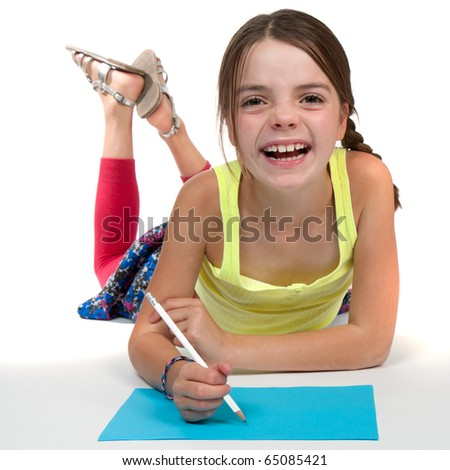 A primary aged girl laughing whilst drawing on some blue paper. - stock photo
