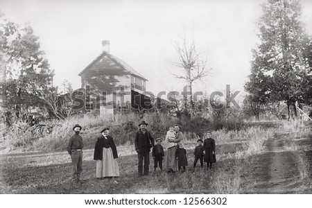 A print from a glass negative taken in an an old view camera about 1890. A group of people standing in front of their house. - stock photo