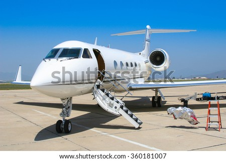 A private jet sits open on the tarmac anticipating the arrival of a couple of pilots.  - stock photo