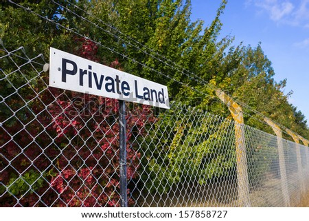 A Private Land notice, on a mesh fence, with barbed wire. - stock photo