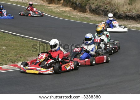 A procession of go karts racing around a bend - stock photo