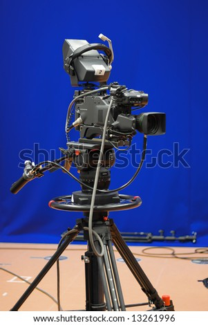 A professional broadcasting television camera in front of a blue screen in a studio. - stock photo