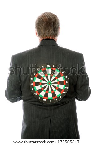 A Professional Business Man stands with a Target on his back. Representing Targeted Business Marketing, Stabbing someone in the back, Target Sales, and other concepts. The perfect image for your needs - stock photo