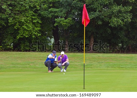 A professional golfer and his caddy reading the green to judge the line of the putt. Series of three photos. - stock photo