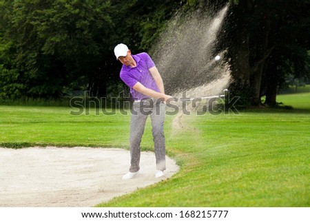 A professional golfer hitting his ball out of a bunker with the sand and ball in mid-air. - stock photo