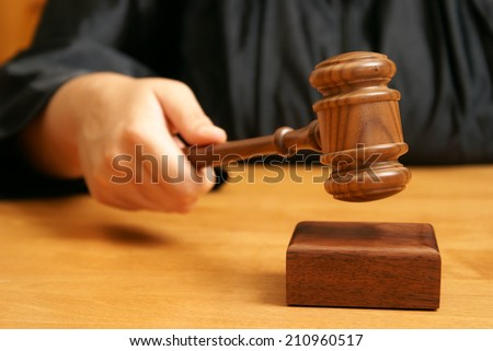 A professional judge declares the legal proceeding with a final hit using the gavel. - stock photo