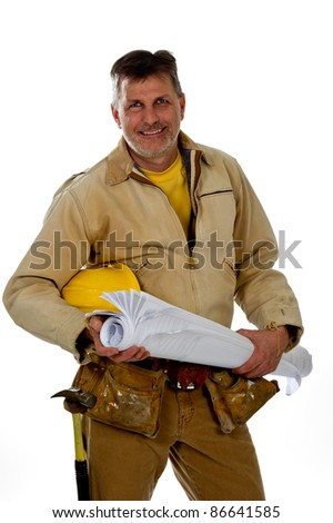 A professional male construction contractor worker wearing a tool belt is holding construction blue print plans and a hard hat. - stock photo