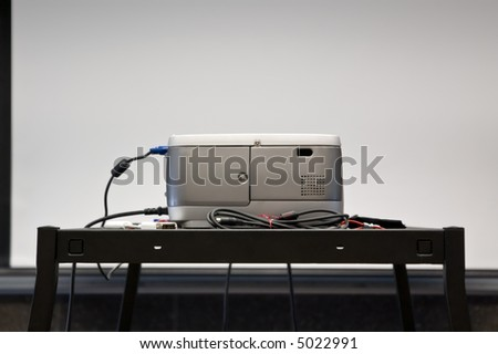 A projector facing a screen in a conference room. - stock photo
