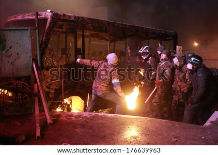 A protester throws a Molotov cocktail at the police. Kyiv, Ukraine, January 19, 2014 - stock photo
